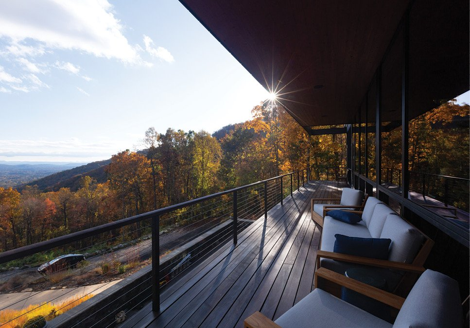 The covered Brazilian ipe wood deck spans the length of the west wing. Cable railing keeps with the modern aesthetic and does not obstruct the long range south-facing views. The sofa and club chairs David sourced from Teak Warehouse.