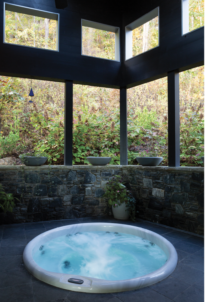 Tucked into the mountain on the north side of the home where the two wings meet, the open-air hot tub spa is a private escape. Just outside, the rising slope is covered with maturing plant growth, which conceals the massive retaining wall.