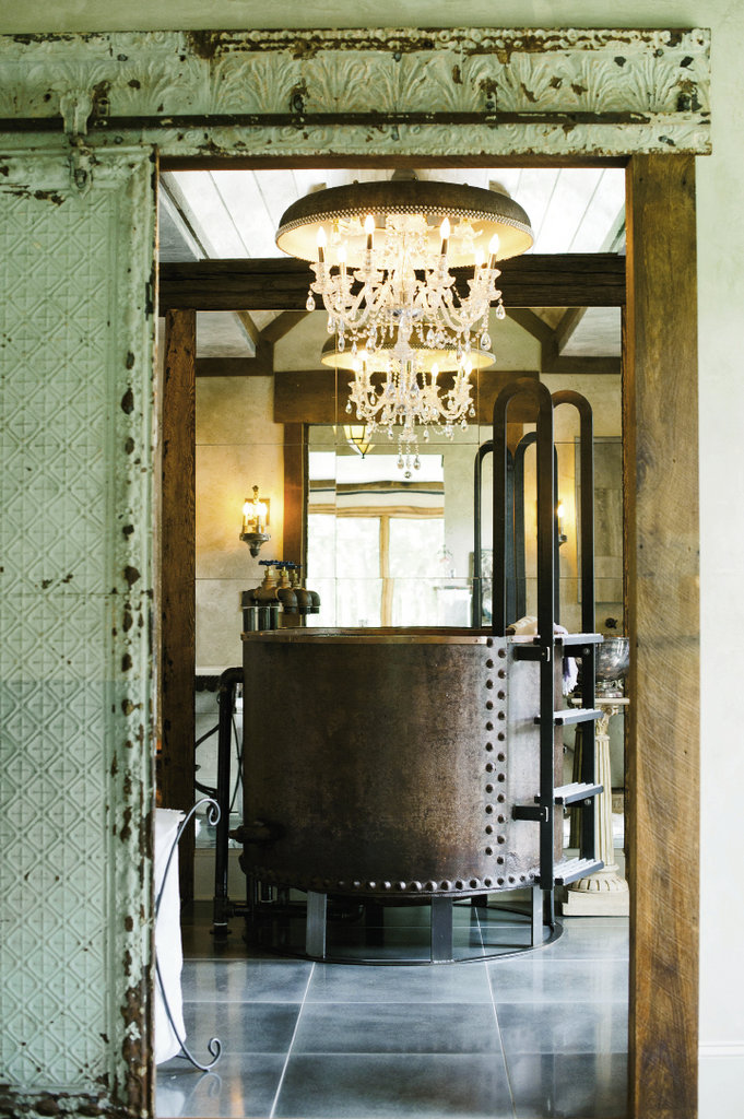 In the master bathroom, a crystal chandelier counters the rustic tub made from an old boiler tank by Oak Hill Iron.