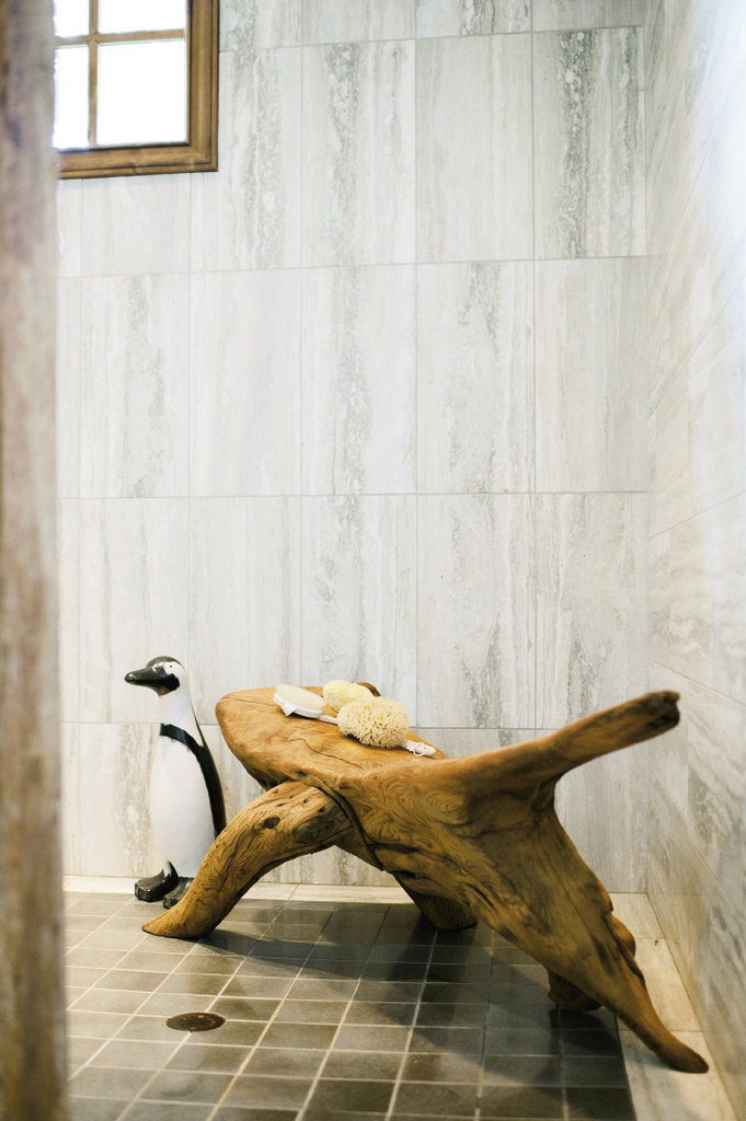 the walk-in shower holds a driftwood bench crafted by an Outer Banks artist, along with a penguin Debra acquired at a retail job
