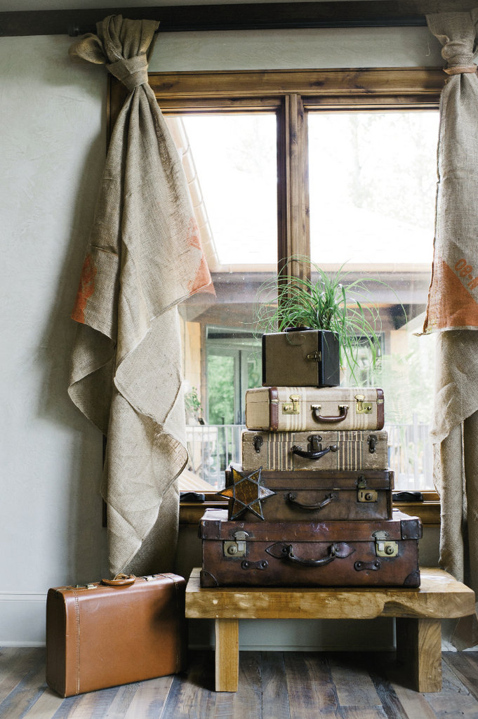 Two burlap tobacco sheets serve as curtains that frame a stack of vintage suitcases.
