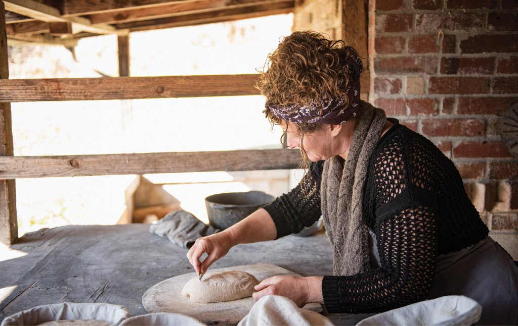 On Your Mark After a morning spent making their own sourdough starters and preparing their loaves, students score their creations before they go into the 700-degree outdoor brick oven.