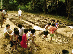 Children use their feet to mix cob, a material made with clay-rich soil, sand, straw, and water, which  is packed into bricks.