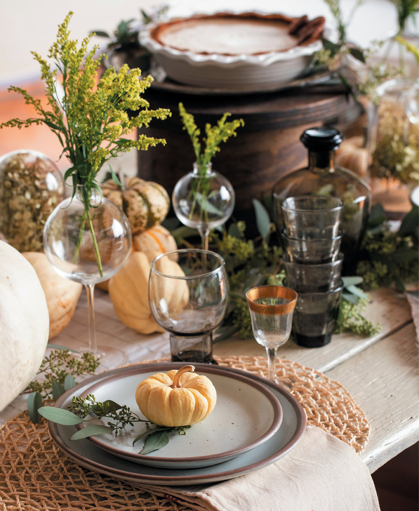 Decorating for fall creates a cozy autumnal vibe. For this table setting, designer Courtney Hinton goes for a neutral palette, blending white pumpkins with natural greenery. Plates by East Fork Pottery; vases and napkins available through Hearth + Home Interiors