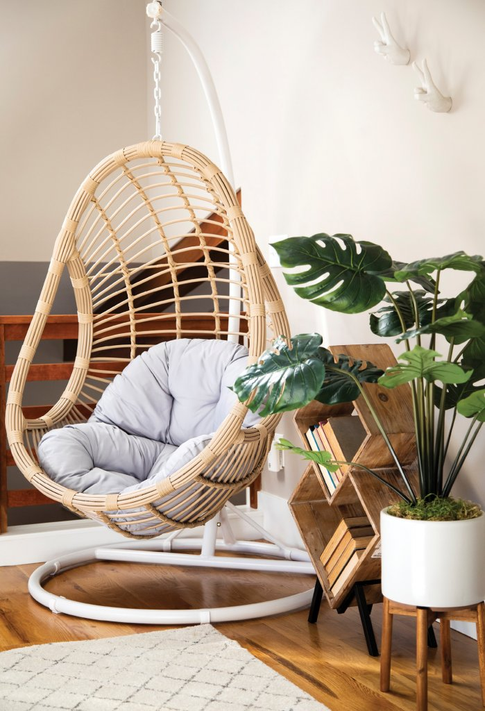 The room is kept light and bright with white and natural elements, including the cozy egg chair.