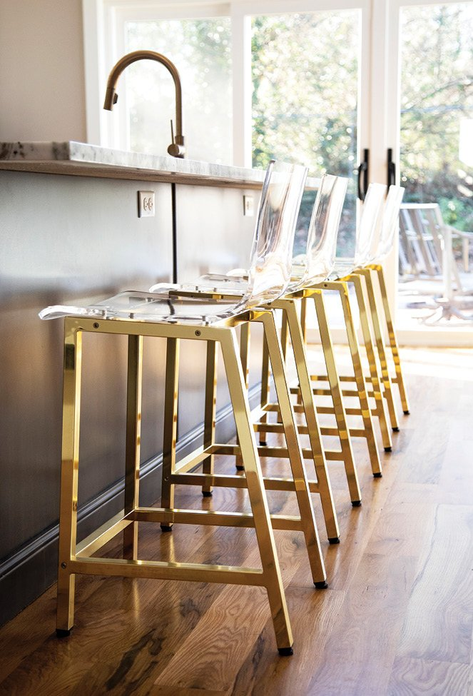 Lucite and gold bar stools add polish to the kitchen.