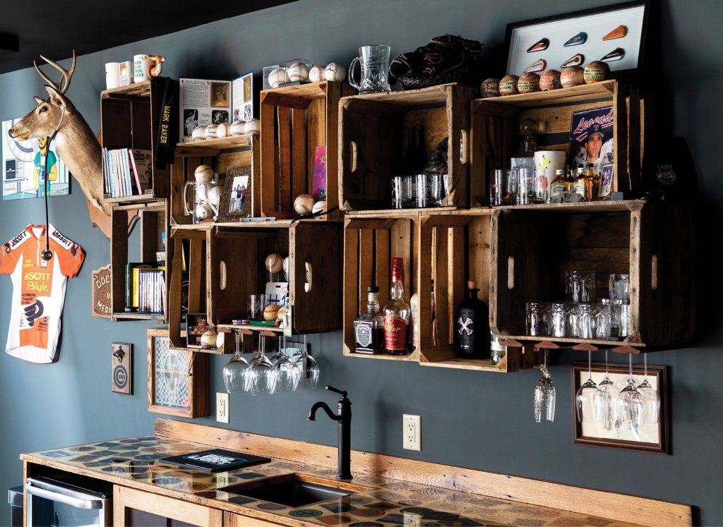 Taking inspiration from dive bars, memorabilia and mementos are displayed in wood crates creatively hung as shelves above the bar.