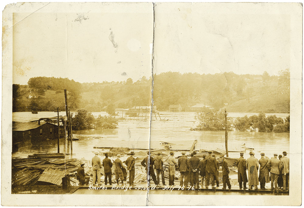 Asheville's industrial district along the French Broad, where massive piles of lumber and other debris choked the river at various places