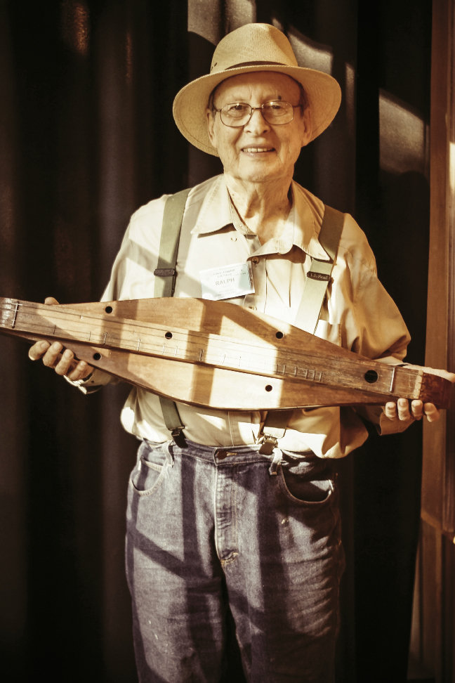 Instructor Ralph Lee Smith, an expert in the history of the mountain dulcimer, holds a circa-1890s instrument from the school's collection.