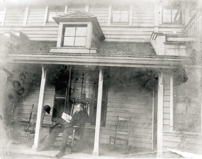 The architect enjoys a book on the porch of Rhododendron, circa 1905.