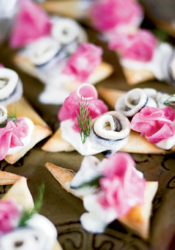 Spanish white anchovies atop puffed crisps with dill, pickled turnips, and crème fraîche and olives by Zambra