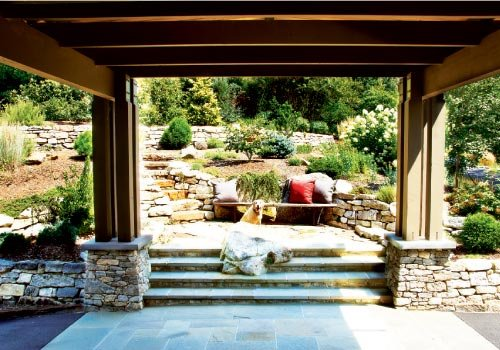Garden Variety: The porte cochere frames a stone landing with a built-in bench. Beyond, a path winds through the terraced landscape.