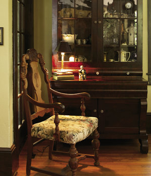 An antique  secretary holds meaningful family objects, from books to a toy bank.