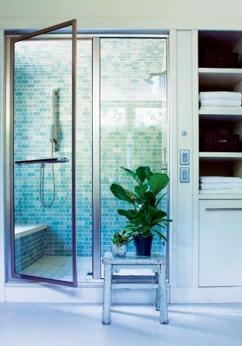 Clean Look: The walk-in shower of the master bath features a custom tile blend in cool tones by Heath Ceramics and a bench by concrete artisans at Mandala Design in Asheville.
