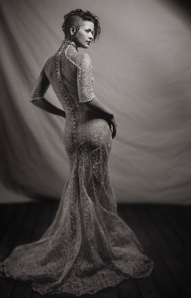 A model shows off Brooke's own high-neck, fit and flare wedding dress she made for herself using a French lace that has sterling silver thread woven into the fabric.