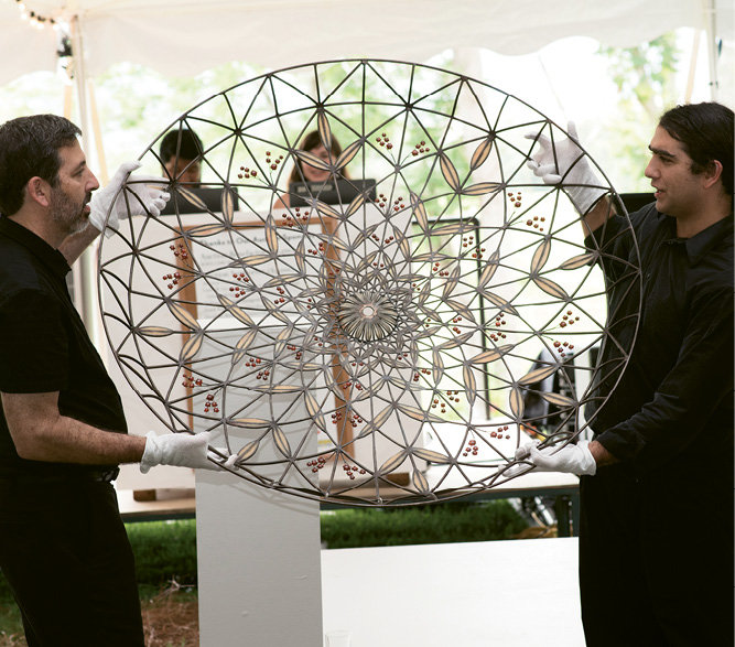 Volunteers Roy Baroff and Shaan Hassan display a sculpture by Kim Cridler.