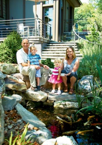 Playing Koi: The backyard, complete with a koi pond, is a place for Paul and Michelle to explore with Sam and Eleni.