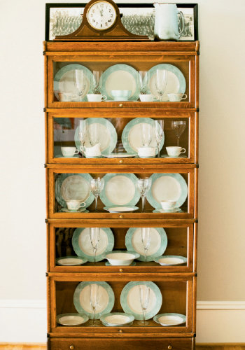 Antique china is showcased in a lawyer's bookcase. A photograph of John's father's World War II military company is displayed atop the case.