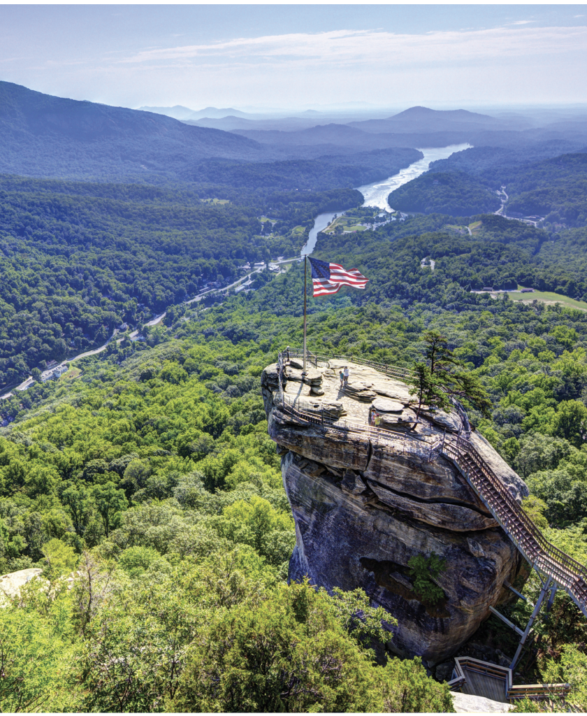 Scene Setter In the Hickory Nut Gorge, the iconic 315-foot granite pillar at Chimney Rock State Park offers breathtaking views over Lake Lure and the Foothills beyond.