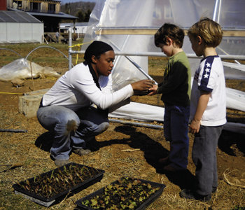 Grower Sherrell Cuthbertson and young gardeners transplant vegetable starts.